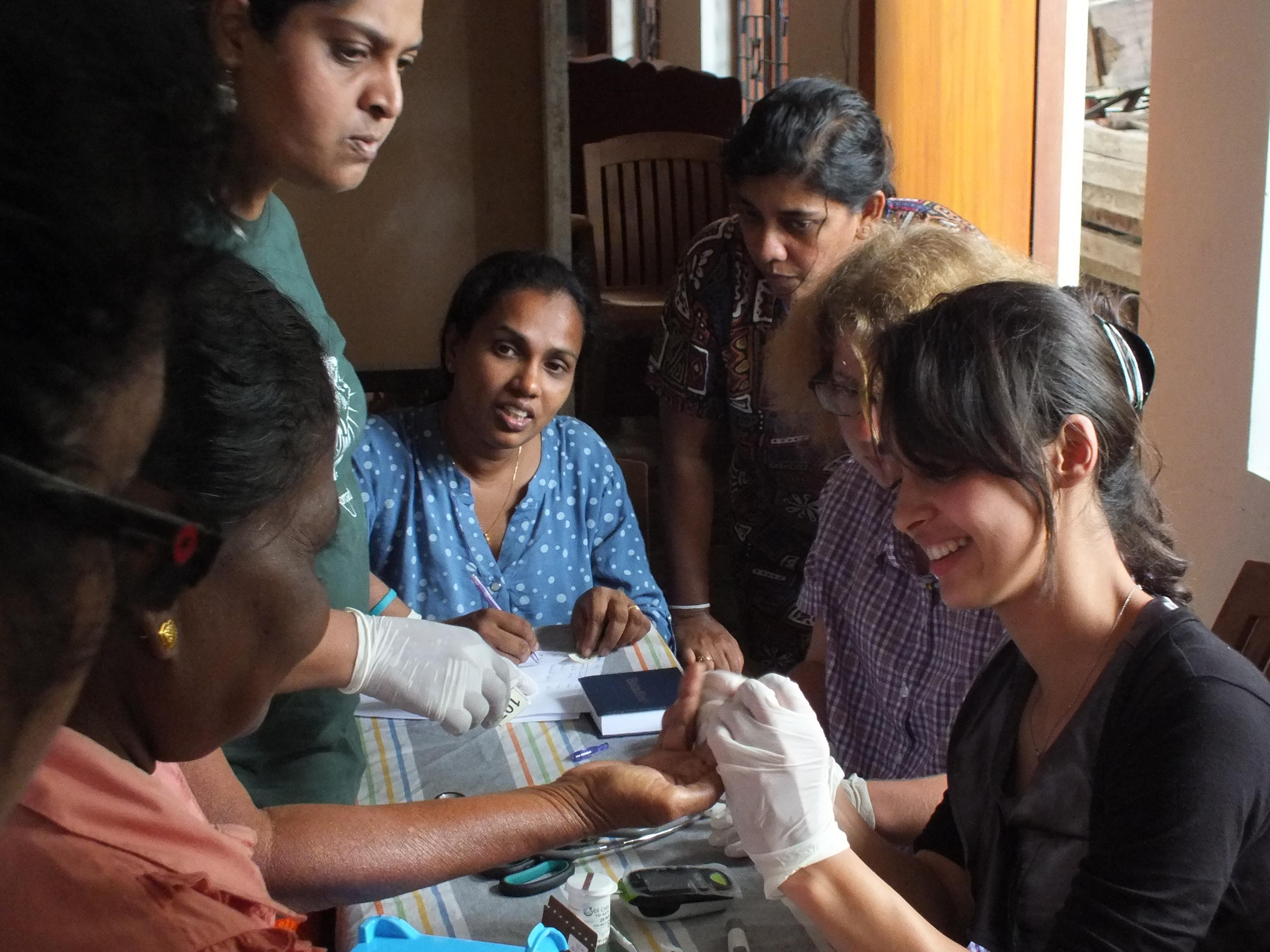 A female intern is pictured helping patients at a medical camp whilst she completes her public health internship in Sri Lanka with Projects Abroad.